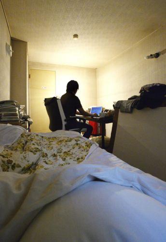 パソコンに向かって一日のほとんどを部屋で過ごす永嶋聡さん。枕元の窓からは朝の光が差し込む=北杜市内