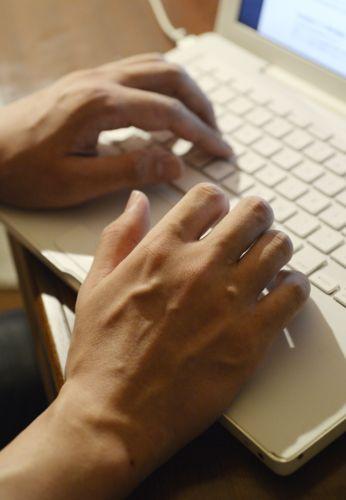 部屋にこもりパソコンの画面に向き合う。インターネットは外とのつながりを保つ貴重なツールだ=北杜市内