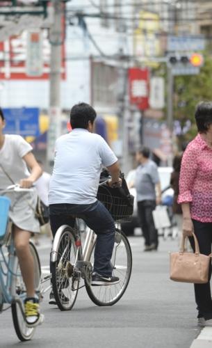自転車で近くの商店街に買い物に行く建一。3年前まで笛吹市の自宅にひきこもっていた=東京都内