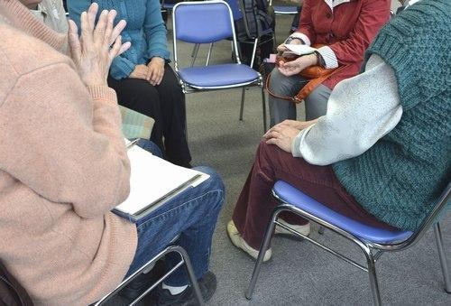 グループミーティングで互いの体験を話す親たち=甲府・県福祉プラザ