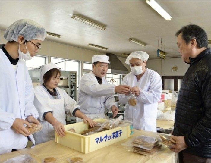 ひきこもりの当事者に焼き上がったせんべいの包装の仕方を教える佐藤邦宏さん(中央)と伊藤正俊さん(右)ら=山形県米沢市