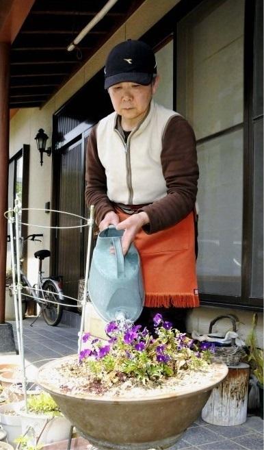 庭の草花に水やりをする遠藤文子さん。狭心症による心室細動で倒れたが、後遺症もなく日常生活を送っている=甲斐市内