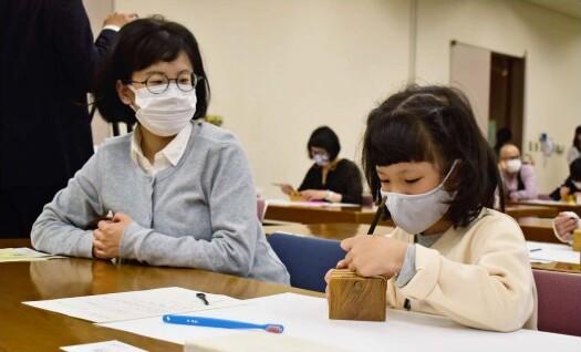 親子連れらがオリジナルの落款印を作った篆刻の体験会=甲府・県立文学館