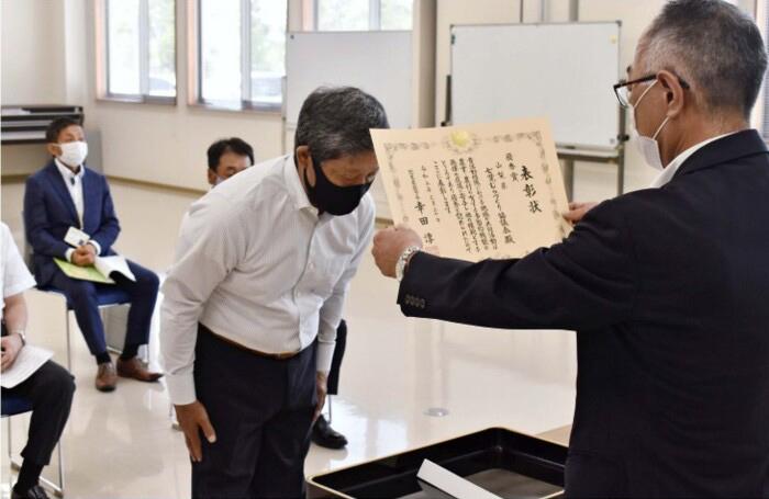 表彰を受ける土橋恵一会長=甲府・中道公民館