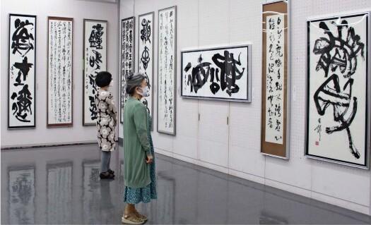 玄遠書道会の役員、一般公募の作品が並ぶ展覧会=甲府・県立美術館
