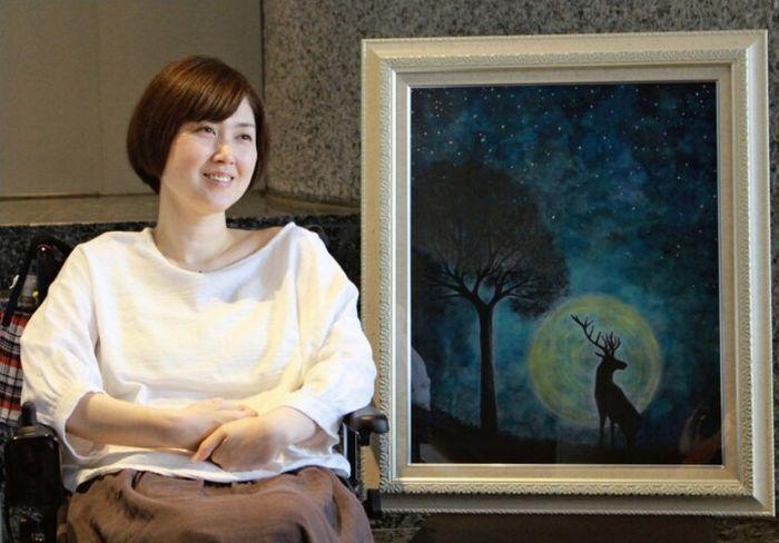個展を開く聖火ランナーの田中千晶さん。両手まひのため、口にくわえた筆と手で制作している=甲府市内