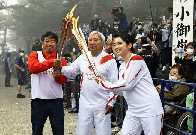 聖火のトーチキスをする、三浦雄一郎さん(中央)と矢野育帆さん(右)=富士山5合目(撮影・広瀬徹)