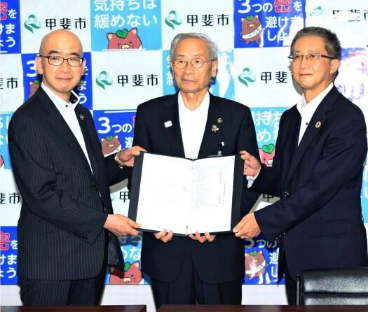 協定書を手に記念撮影する保坂武市長(中央)ら=甲斐市役所
