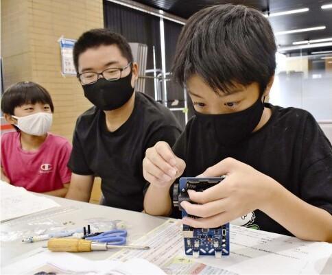 小中学生14人が参加した「プログラミングカー」を作る教室=甲府・県生涯学習推進センター