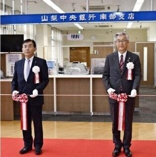 テープカットに臨む山梨中央銀行の関光良頭取(右)と佐野和広南部町長=南部町役場分庁舎