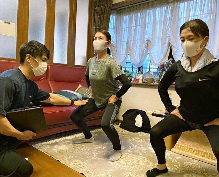 試験的に実施した派遣型のパーソナルトレーニングで利用者を指導するトレーナー(左)=甲府市川田町