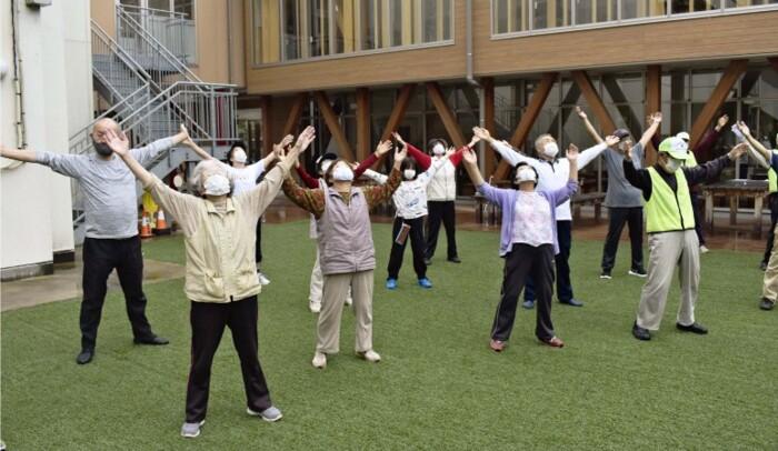 ラジオ体操で体を動かす会員ら=大月短大