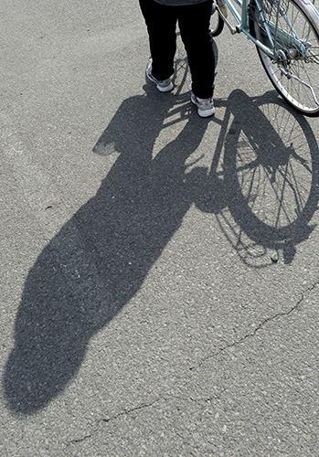自転車を引いて歩くサトコ。ひきこもりから脱して、「前に進みたい」と願う=国中地域(撮影・広瀬徹)