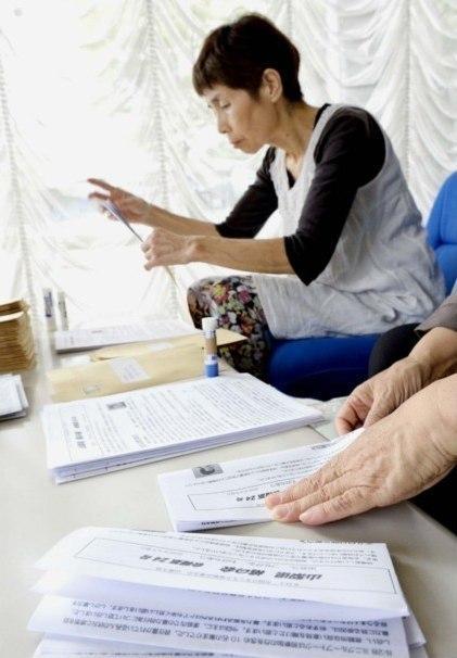 会報の発送準備をする山梨県桃の会のスタッフ。会報では、ひきこもりの本人や親を孤立させないために始めた「アウトリーチ」の活動を紹介している=甲府市内
