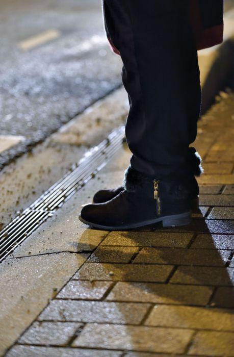 娘から贈られたブーツを履いてたたずむアヤミさん。親思いの子が唯一、無理を言ってほしがったのがスマートフォンだった=甲府市内