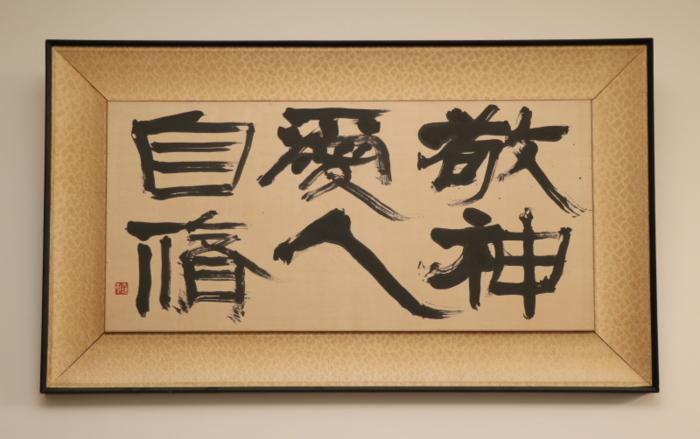 校長室に掲げられている「敬神 愛人 自修」の校訓。書家大橋南郭氏が揮毫したもので、この書が卒業証書にも使われている