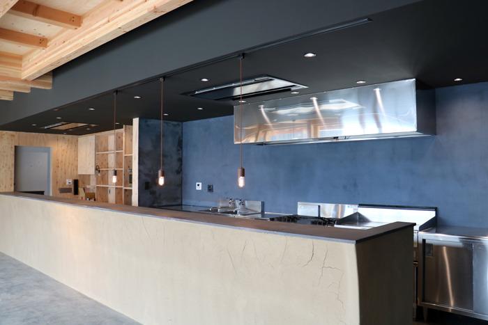 バーカウンターやキッチン、事務室などを備えた、土壁が目を引く交流棟1階