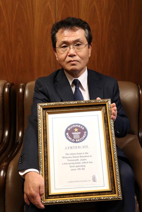 「世界で最も古い歴史を持つ温泉宿」としてのギネスブック認定書を持つ川野さん