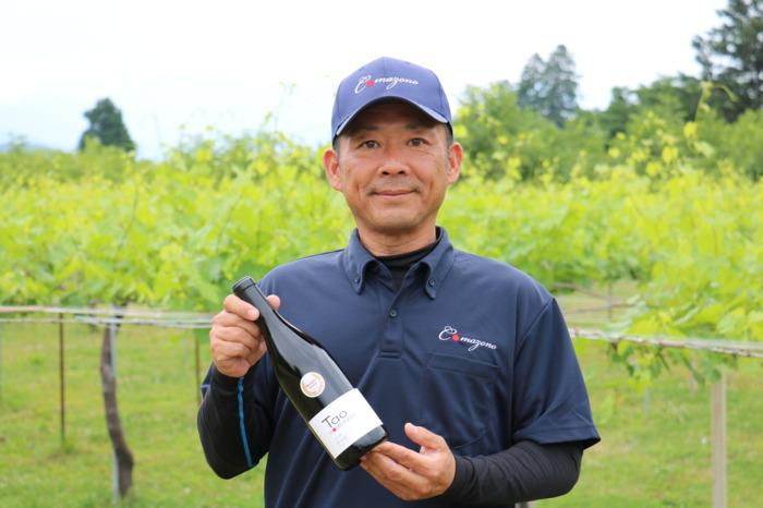 自社畑・駒園の前で、サクラアワードの「ベストジャパニーズワイン」に選ばれたワイン「Tao 甲州駒園2018」を持つ駒園ヴィンヤード社長の近藤修通さん