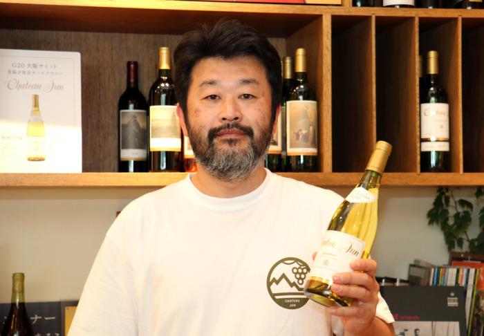 G20首脳夕食会で提供された甲州種ワインを手に持ち、ワイン造りの思いを語るシャトージュンの仁林欣也さん