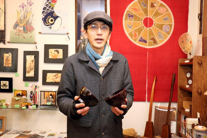 「人気品のこのおわんは、使い込むほどにピカピカになります」と話す日本の匠と美ほさか店主の保坂浩輝さん。右手に持っているおわんが新品で、左手のつやのあるのが使い込んだものだという