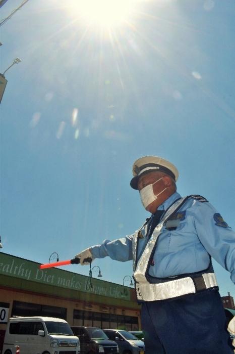 猛暑の強い日差しの中、新型コロナ対策のマスクをつけて車を誘導する警備員=甲府市内