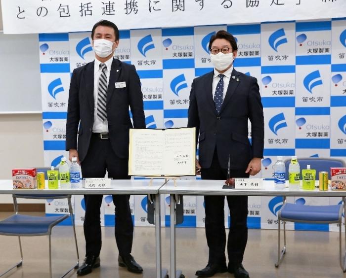 協定書に署名した山下政樹市長(右)と池内呉郎東京支店長=笛吹市役所
