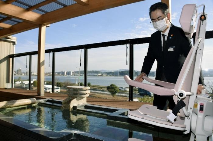 客室の露天風呂で入浴用補助設備を操作する勝谷有史さん=松江市