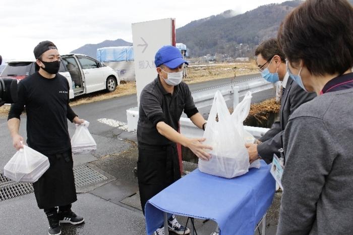 カルビ弁当を手渡す梶原直人社長(中央)=富士吉田市立病院前