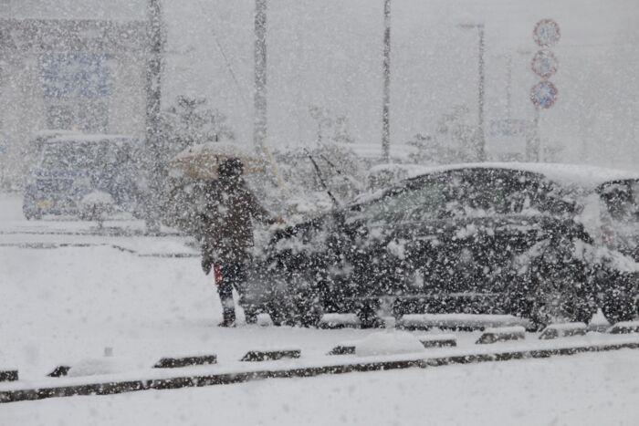 車に積もった雪を取り除く女性=富士吉田市内