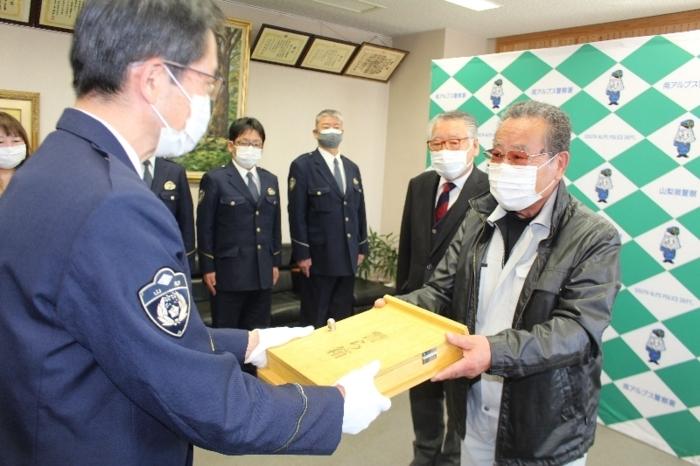 秋山敦署長に警ら箱を手渡す依田健さん(右)=南アルプス署
