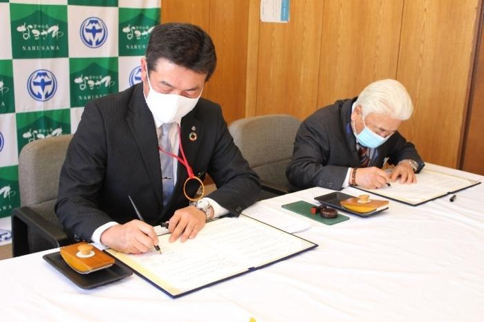 協定書に署名する小林優村長(右)=鳴沢村役場