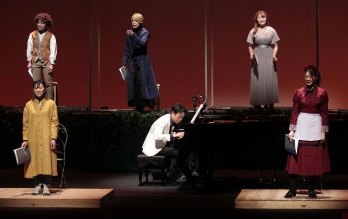 情感たっぷりに演じる出演者とピアノを演奏する小林真人さん(下段中央)=甲府・YCC県民文化ホール