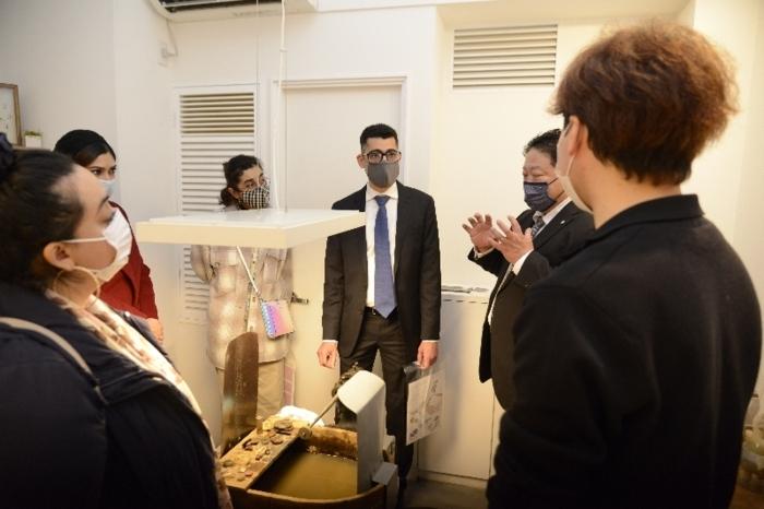 職人から説明を受けるバーレーン大使館のマハムード・アブドウルアール次席(中央)=甲府市丸の内1丁目