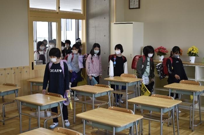 新しい教室で自分の席を探す児童=甲府市上曽根町