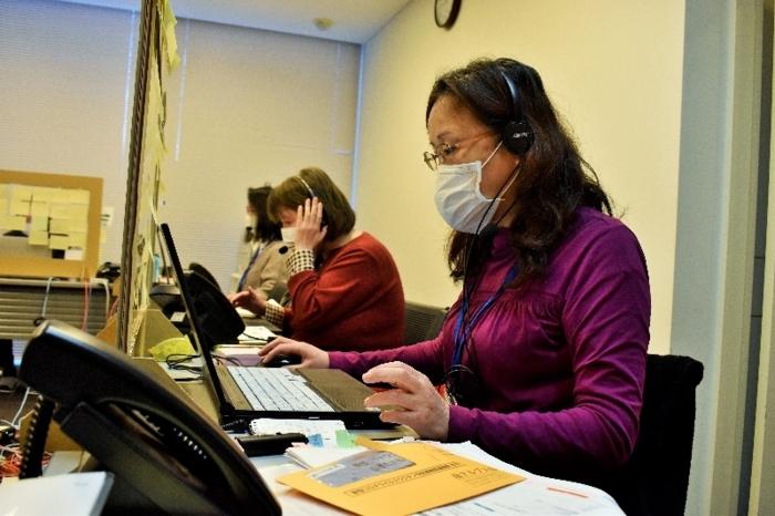 ワクチン接種の予約に対応するスタッフ=南アルプス・市健康福祉センター