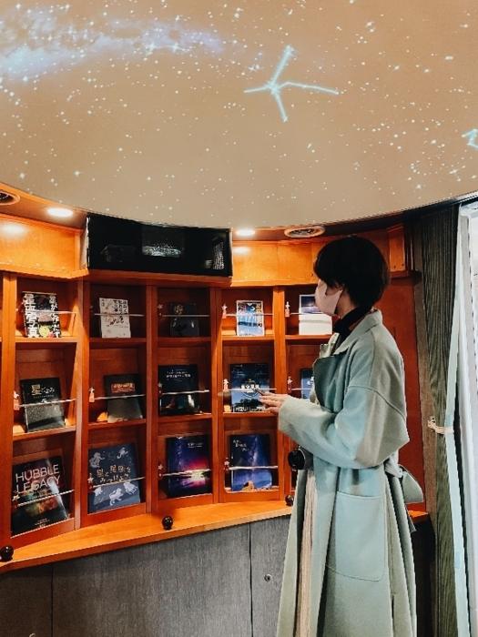 車内にあるギャラリーで、星にまつわる本を選ぶ友人