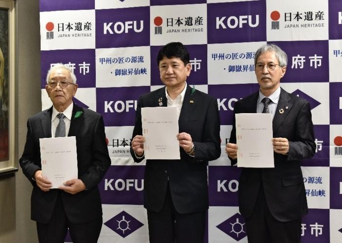 協定書を手にする(右から)中尾均社長、樋口雄一市長、相沢康雄会長=甲府市役所