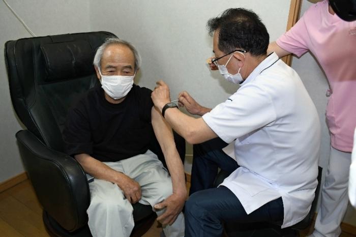 ワクチン接種を受ける高齢者(左)=北杜市白州町白須