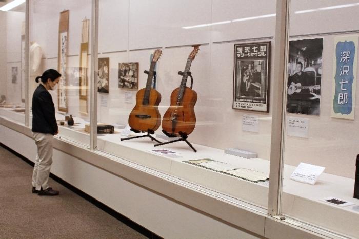 作家デビュー前にギタリストとして活躍していた深沢七郎のコーナーには、ギターが並ぶ=甲府・県立文学館