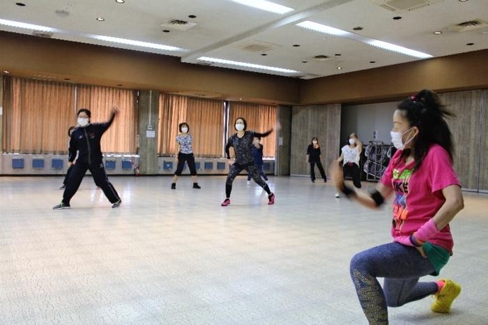 音楽に合わせて体を動かす参加者=中央市布施