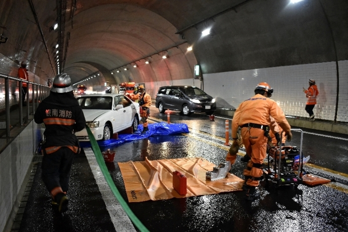 訓練で、スプリンクラーでの水散布後に負傷者の救助に向かう消防署の職員=中部横断自動車道樽峠トンネル