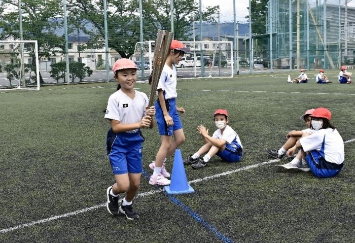 実際に使われたトーチで聖火リレーを体験する児童=甲府・駿台甲府小