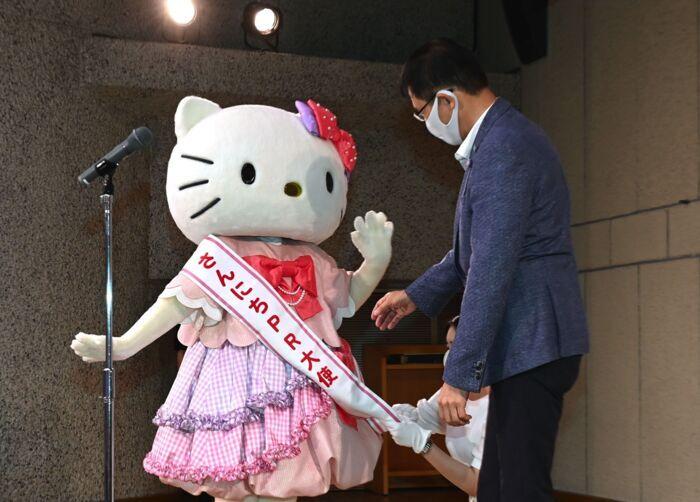 「さんにちPR大使」のたすき受け取る人気キャラクター「ハローキティ」=甲府・山日YBS本社