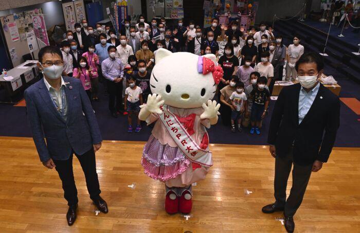 「さんにちPR大使」のたすき受け取り、来場者らと記念撮影する人気キャラクター「ハローキティ」=甲府・山日YBS本社