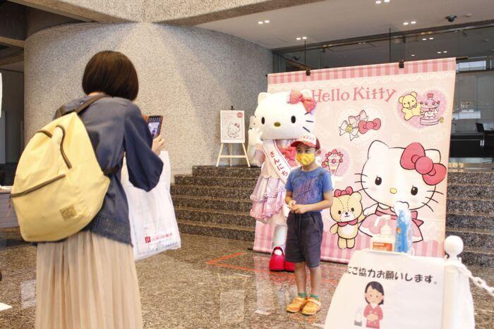 サンリオの人気キャラクター「ハローキティ」との記念撮影を楽しむ親子=甲府・山日YBS本社