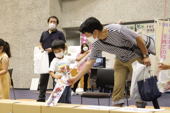 新聞紙のプールからお菓子などを探す親子=甲府・山日YBS本社