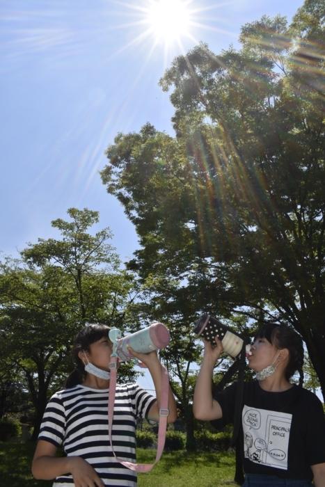 日陰で水分を補給する小学生=甲府・緑が丘スポーツ公園