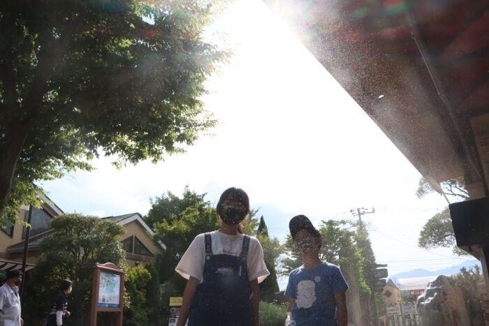 強い日差しの中、ミストで涼を感じる子ども=甲州市勝沼町等々力