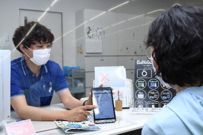 電子書籍の貸し出しサービスについて説明する男性司書(左)=韮崎市立大村記念図書館